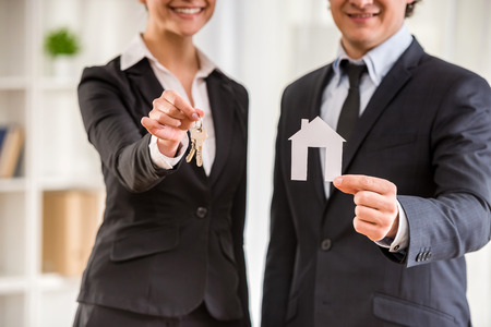 Twee makelaars in kostuums tonen een model van huis en sleutels. Stockfoto