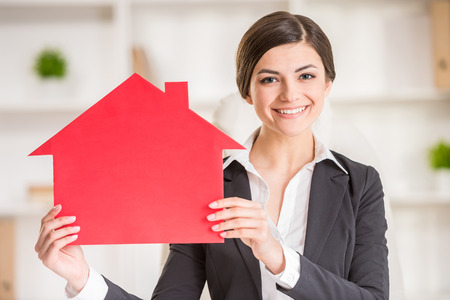 home for sale sign: Happy  woman is showing home for sale sign. Stock Photo