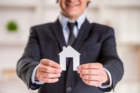 man is holding model of home. photo