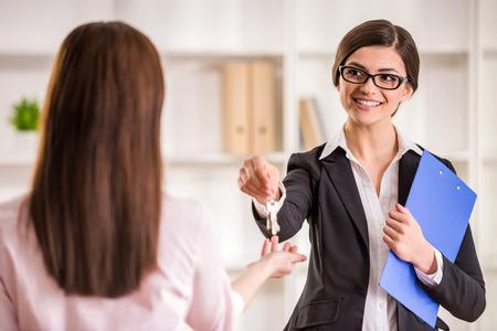 agente comercial: Mujer feliz que da clave a un nuevo propietario de un apartamento.