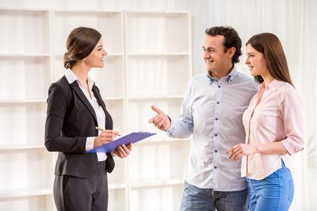 agente comercial: Joven pareja hablando con el agente de bienes raíces.