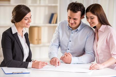 Jonge uitleggen huurovereenkomst aan jonge paar. Stockfoto