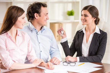 property management: Young couple signed financial contract with female realtor.