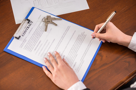 Close-up hand of young woman is signing a conract to apartments.