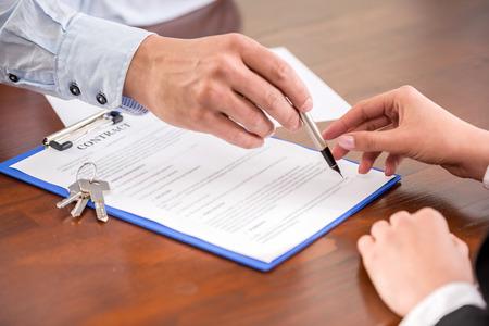 contrato de trabajo: Mujer joven es la firma de contrato financiero con inmobiliaria masculino. Acercamiento. Foto de archivo