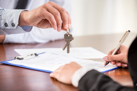 firmando: Mujer joven es la firma de contrato financiero con inmobiliaria masculino. Acercamiento. Foto de archivo