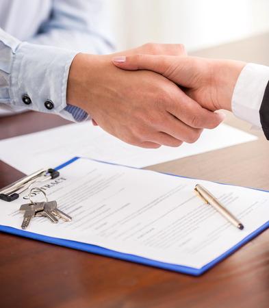 contratos: Apretón de manos de un agente de bienes raíces y un cliente. Foto de archivo