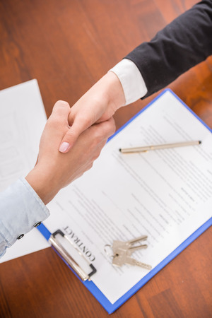 real estate contract: Top view of handshake of a real estate agent and a client.
