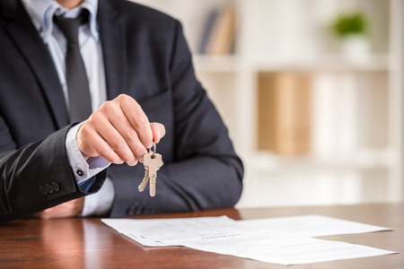 accommodation broker: Close-up of hand of man is holding a key from a new apartment.