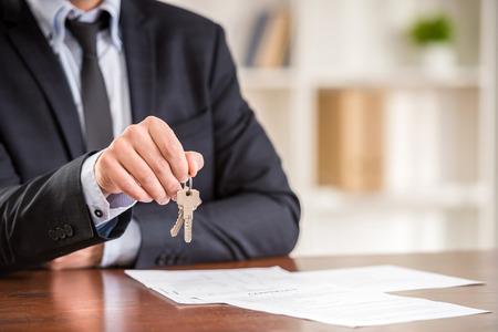 Close-up van de hand van de man houdt een sleutel van een nieuw appartement.