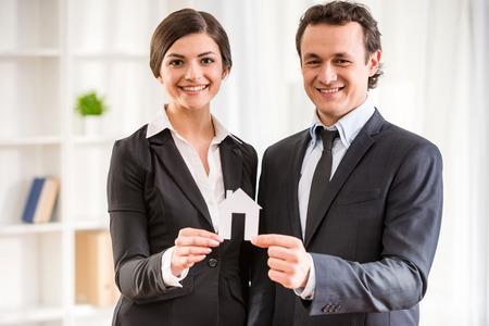 양복 입은 두 명의 부동산 중개인이 집 모델을 보여주고 있습니다.