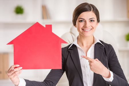 home for sale sign: Happy realtor woman is showing home for sale sign. Stock Photo