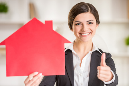 Happy realtor woman is showing home for sale sign and thumbs up. Foto de archivo