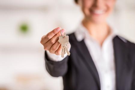 agente comercial: Realtor está dando las llaves de un apartamento a los clientes. Centrarse en las teclas.