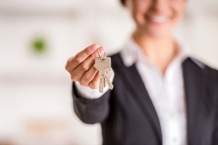 property management: Realtor is giving the keys to an apartment to clients. Focus on the keys. Stock Photo