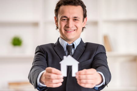 Smiling realtor man is holding a model of home. photo