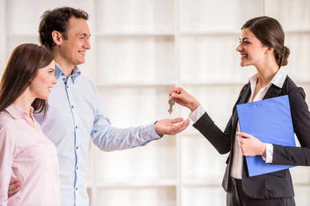 realtor: Female realtor is giving to young couple a key from new flat.