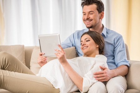 homme enceinte: Jeune couple heureux attend un b�b�. Ils utilisent une tablette.