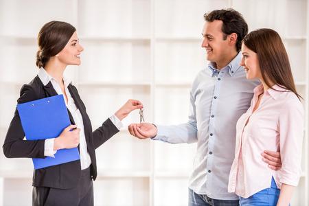 personas unidas: Agente de bienes ra�ces Mujer est� dando a la joven pareja una llave del piso nuevo. Foto de archivo