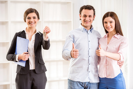thumb keys: Portrait of happy young couple are showing thumb up and female realtor with keys in a new flat.