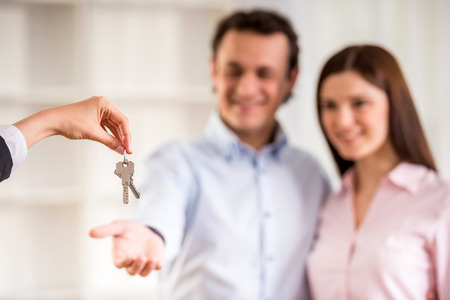agente comercial: El hombre con su mujer le está dando una llave de la casa.