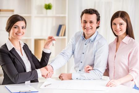 Het jonge paar ondertekening financiële contract met vrouwelijke makelaar.