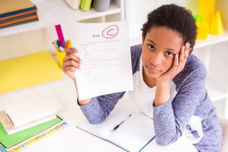 Unhappy mulatto schoolgirl sitting at the table and  showing  bad test results on colorful background. Stockfoto