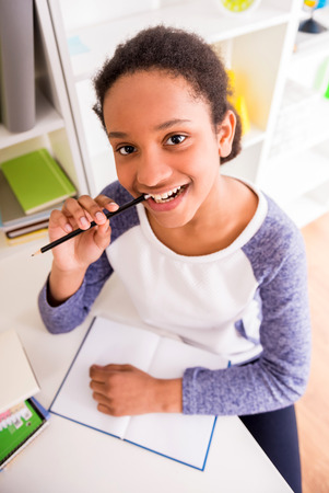 mulatto: Young pretty smiling mulatto schoolgirl sitting at the table and holding a pencil in hand on colorful background. Stock Photo