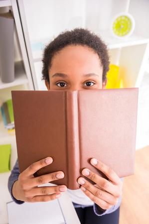 ni�os inteligentes: Colegiala joven mulata bonita que se sienta en la mesa y con un libro en las manos en el fondo colorido.