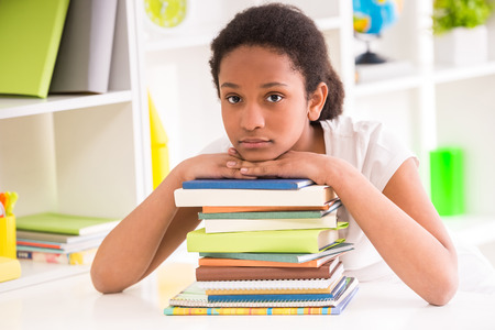 mulatto: Young sad mulatto schoolgirl sitting at the table with stack of books on colorful background.