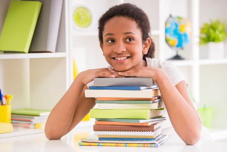 colegiala: Colegiala joven mulata sonriente sentado en la mesa con la pila de libros sobre el fondo colorido.
