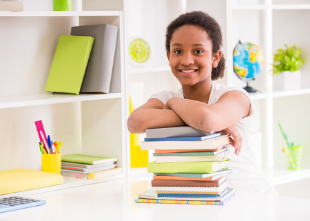 kids reading book: Young smiling mulatto schoolgirl sitting at the table with stack of books on colorful background.