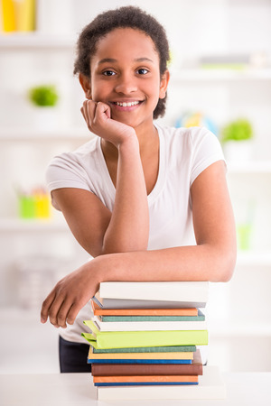 mulatto: Young smiling mulatto schoolgirl standing with stack of books on colorful background. Stock Photo