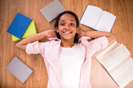 mulatto: Young smiling mulatto schoolgirl laying on the floor with some color books.
