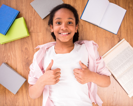 mulatto: Young smiling mulatto schoolgirl laying on the floor with some  and making thumbs up.