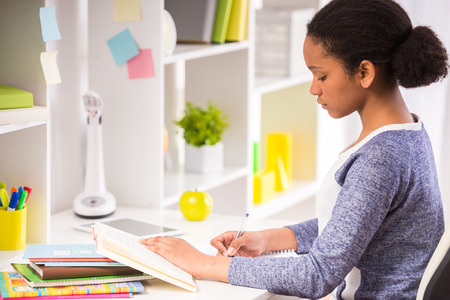 mulatto: Young pretty  mulatto schoolgirl sitting at the table and writing homework on colorful background. Stock Photo