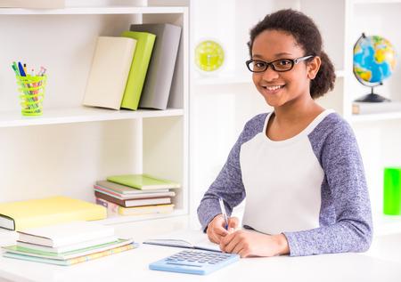 colegiala: Colegiala mulato joven en los vidrios que se sientan en la mesa y escribiendo la tarea en el fondo colorido.