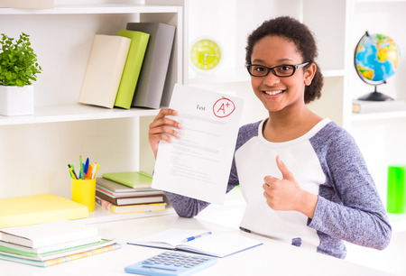 test result: Young mulatto schoolgirl  in glasses sitting at the table and  showing perfect test results on colorful background.