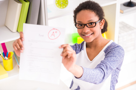 mulatto: Young mulatto schoolgirl  in glasses sitting at the table and  showing perfect test results on colorful background.