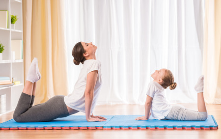 yoga white: Mother and daughter doing yoga exercises on rug at home.