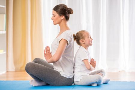 haciendo ejercicio: Madre e hija haciendo ejercicios de yoga sobre la alfombra en casa. Foto de archivo