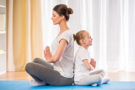 doing: Mother and daughter doing yoga exercises on rug at home.