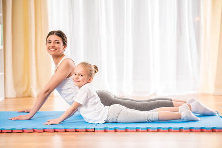 Mother and daughter doing yoga exercises on rug at home. photo