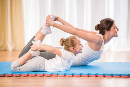 kids activities: Mother and daughter doing yoga exercises on rug at home.