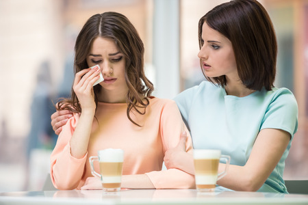friend hug: Young girl talking with her upset friend and holding her shoulders in cafe. Stock Photo