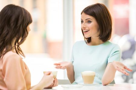 2 美しい少女コーヒーと都市のカフェに座っていると話しています。 写真素材