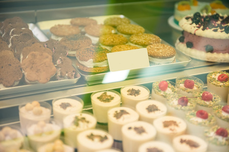 window display: Pastry shop display window with variety of  tasty desserts. Stock Photo