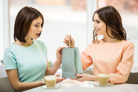 two friends: Young beautiful girl sitting in cafe with her friend and receiving a pack with gift.