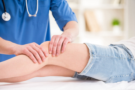 Close-up of male physiotherapist massaging the  leg of female patient in a physio room.