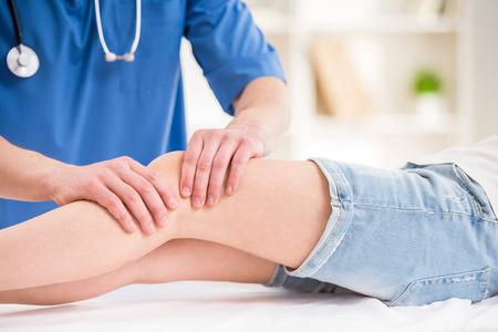 de rodillas: Primer plano de fisioterapeuta masculino masajear la pierna del paciente en una sala de fisioterapia.